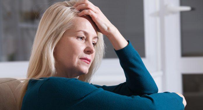 Λυπημένη μέσης ηλικίας γυναίκα κάθεται στον καναπέ του σπιτιού της