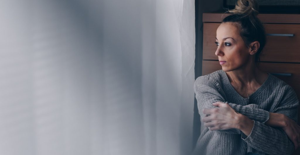 Γυναίκα καταθλιπτική που κοιτάζει έξω από το παράθυρο