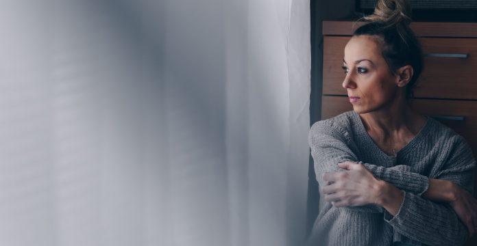 Αγχωμένη γυναίκα που κοιτάζει έξω από το παράθυρο