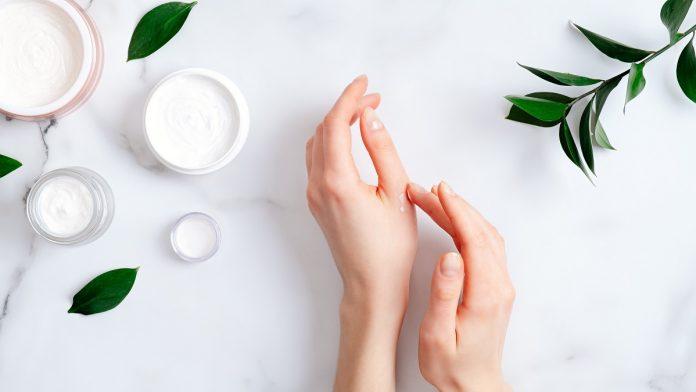 γυναίκα περιποιείται τα χέρια της με κρέμα χεριών