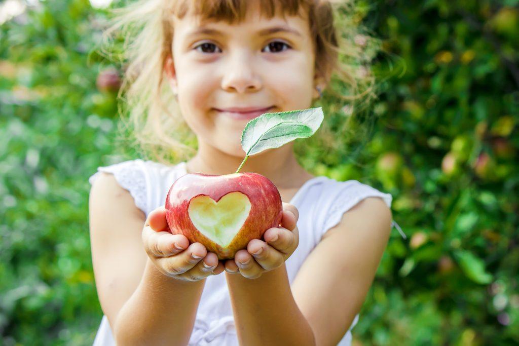 Κορίτσι που κρατάει ένα μήλο σε σχήμα καρδιάς