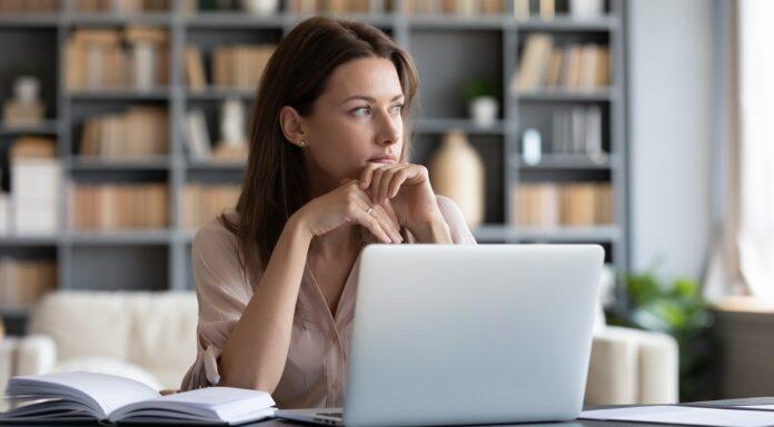 Σκεφτική γυναίκα κάθεται στο γραφείο